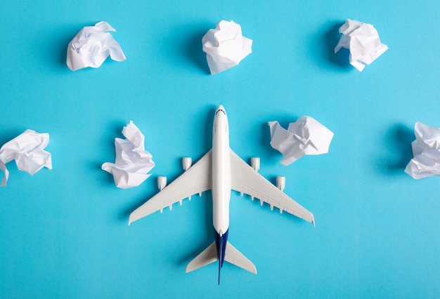 Modelo de avión volando entre nubes de papel