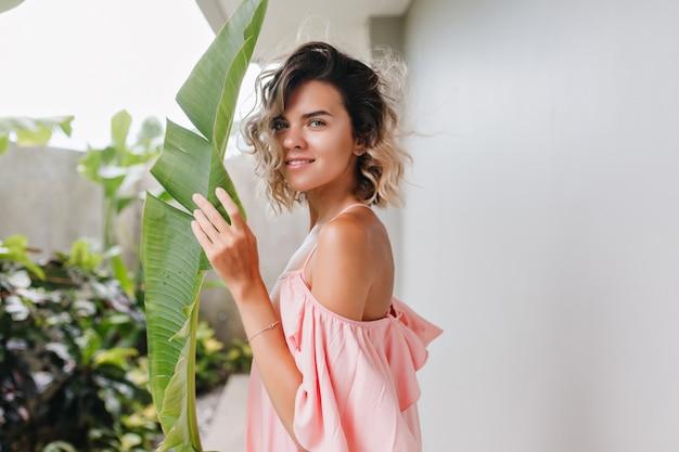 Modelo bastante femenino con ojos azules mirando y sosteniendo la hoja verde. adorable chica bronceada con expresión de cara tranquila de pie en el patio.
