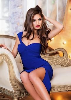 Modelo blanco sexy en elegante vestido azul sentado en el sofá en el interior de lujo en estudio