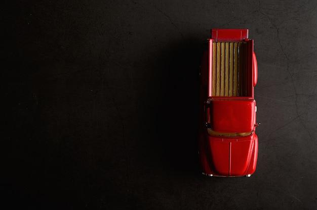 Modelo de camioneta roja en el piso negro