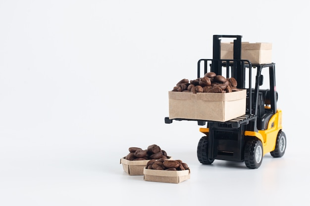 Modelo de carretilla elevadora en miniatura cargando cajas de cartón que contienen granos de café aislados