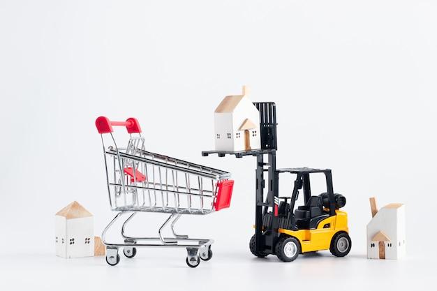 Modelo de carretilla elevadora en miniatura cargando la casa de carga al carro de compras rojo aislado sobre fondo blanco.