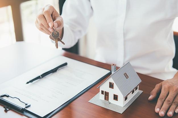 Modelo de casa con un agente de bienes raíces y un cliente discutiendo un contrato para comprar una casa