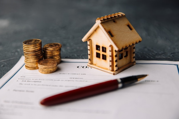 Modelo de casa con agente de bienes raíces y cliente discutiendo por contrato para comprar casa