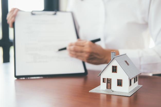 Modelo de casa con agente inmobiliario y cliente discutiendo por contrato para comprar casa,