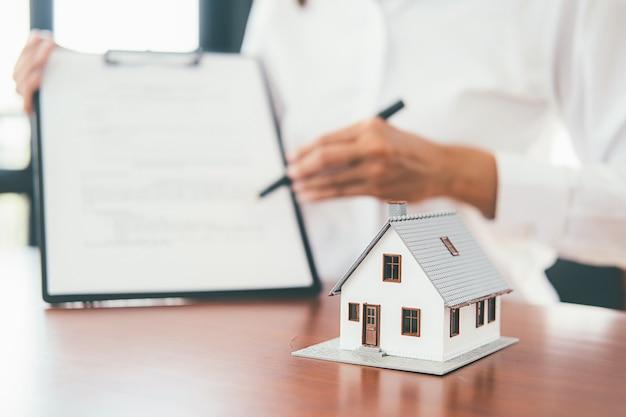 Modelo de casa con agente inmobiliario y cliente discutiendo sobre el contrato para comprar casa, seguro o préstamo inmobiliario.