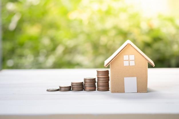 Modelo de casa con aumento del gráfico de monedas apiladas en zonas verdes foco suave