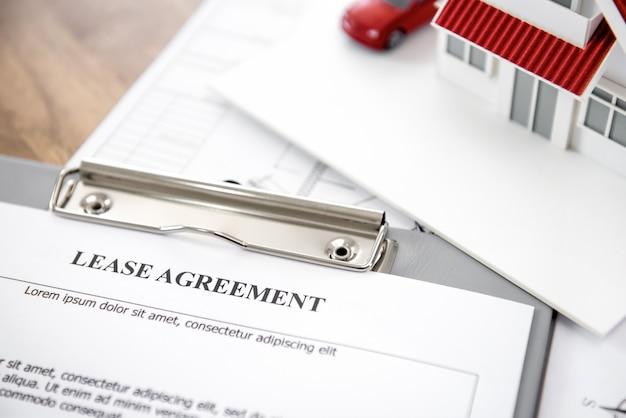 Modelo de casa y automóvil con papel de contrato de arrendamiento