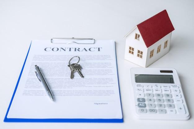 Modelo de la casa, calculadora y llave de la casa en contrato de bienes raíces