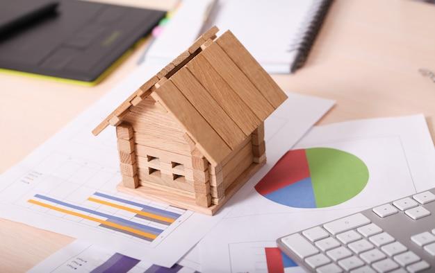 Modelo de casa y calculadora en plan de construcción