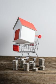 Modelo de casa en carro de compras y hilera de monedas.