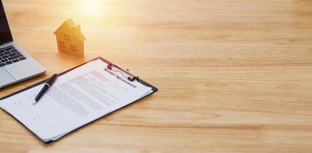 Modelo de casa cerca de documento de contrato de arrendamiento o alquiler y computadora portátil con espacio de copia, negocio inmobiliario concepto de compra, préstamo o inversión