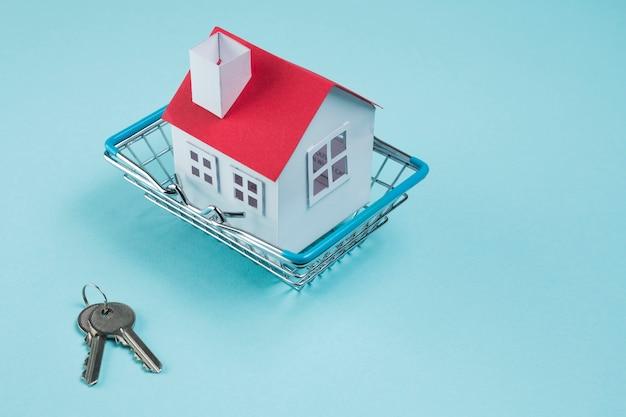 Modelo de casa en cesto metálico y llaves sobre fondo azul.