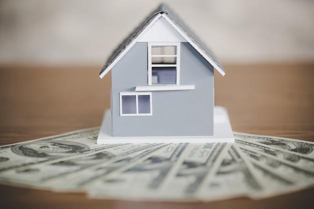Modelo de casa clásica en dólar en mesa de madera
