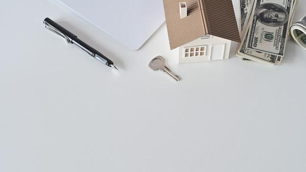 Modelo de casa, contrato de alquiler o compra de contratos de vivienda, dinero, bolígrafo con la propiedad clave en la mesa blanca de espacio de copia.