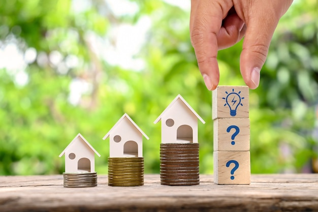 Modelo de la casa en el dinero y la mano del inversor que sostiene el bloque de madera con el concepto creciente del dinero del icono de la bombilla y de la compra de la casa o del condominio