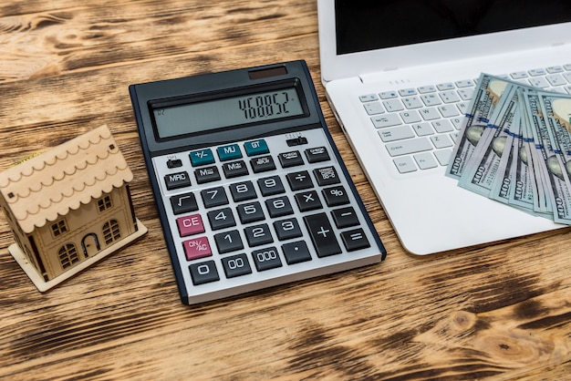 Modelo de casa con dólares, portátil y portapapeles