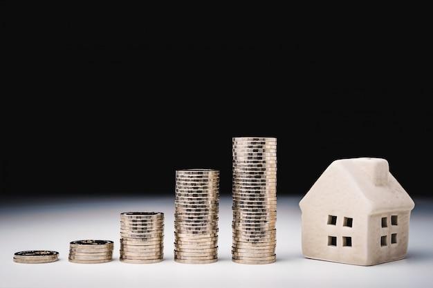 Modelo de casa y hilera de monedas en mesa blanca