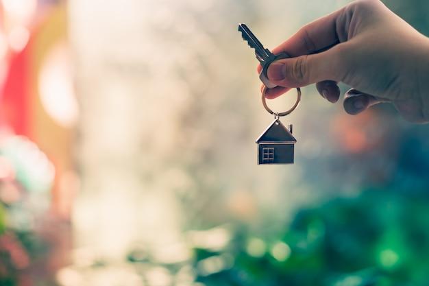 Modelo de casa y llave en agente de seguros de hogar.