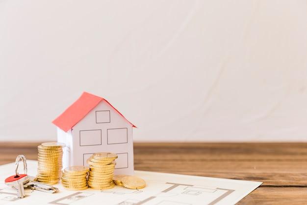Modelo de la casa, llave y monedas apiladas en blueprint