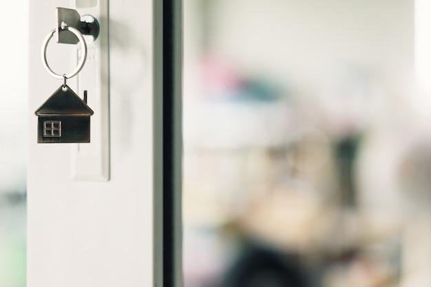 Modelo de casa con llave en la puerta de la casa