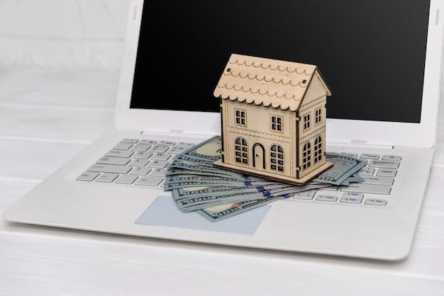 Modelo de casa de madera con billetes de dólar en el teclado del ordenador portátil
