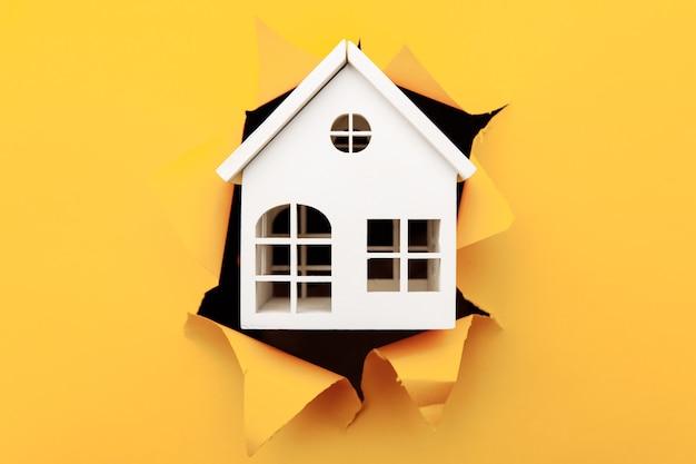 Modelo de casa de madera blanca a través de un primer plano de agujero de papel amarillo.