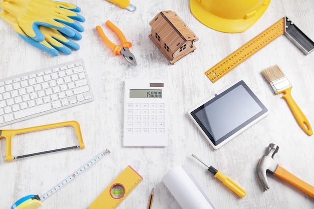 Modelo de casa de madera con calculadora y otros objetos.