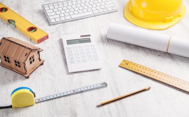 Modelo de casa de madera con casco y calculadora.
