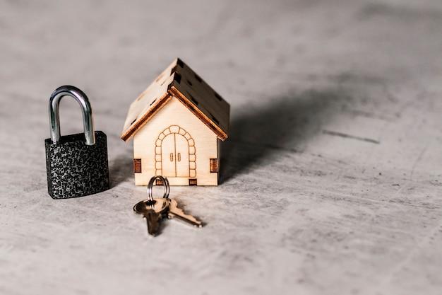 Modelo de una casa de madera con cerradura y llaves.