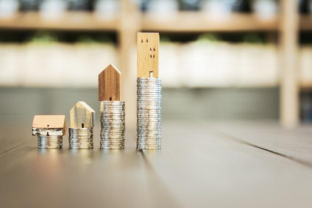 Modelo de casa de madera y fila de monedas de dinero sobre fondo blanco