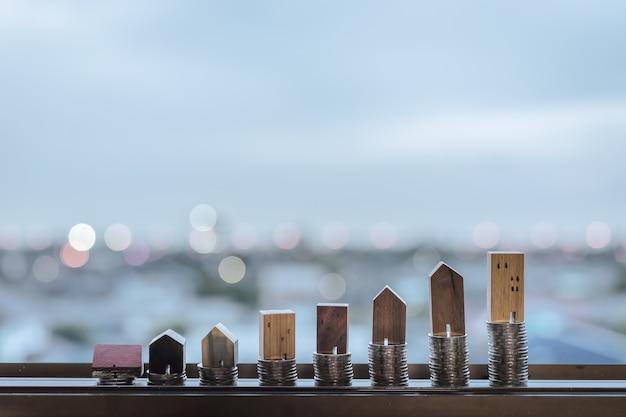 Modelo de casa de madera y fila de monedas en mesa de madera con fondo azul claro, real esta