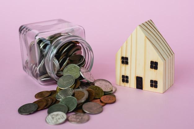 Modelo de casa de madera con monedas de dinero en el frasco de vidrio sobre fondo rosa con espacio de copia para negocios y finanzas por concepto de propiedad