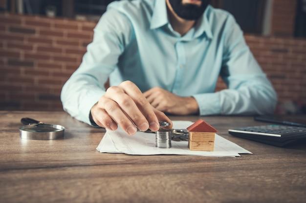Modelo de casa de madera con monedas o concepto inmobiliario