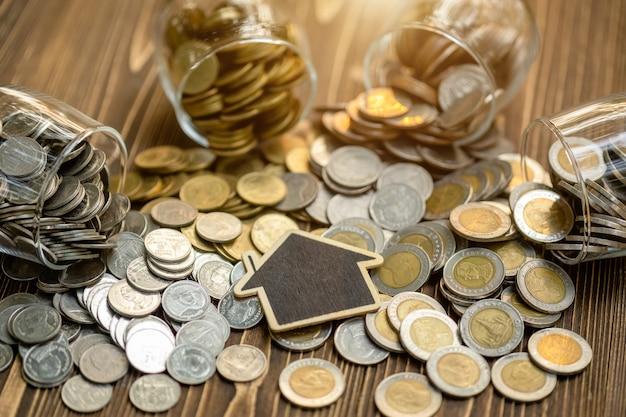 Modelo de la casa de madera y pila de monedas en la mesa de madera. ahorro de dinero para el concepto de hogar
