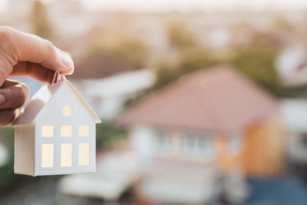 Modelo de la casa en la mano del agente del agente de seguros de hogar o en la persona del vendedor.