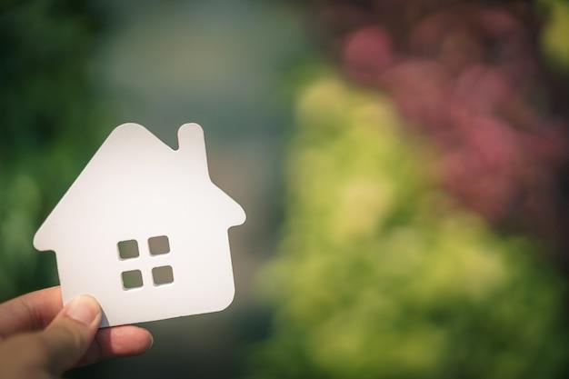Modelo de casa en la mano del agente de corredores de seguros de hogar
