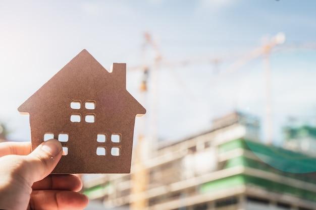 Modelo de la casa en la mano del agente de seguros de hogar o en persona del vendedor.