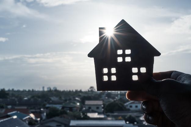 Modelo de la casa en la mano del agente de seguros de hogar o en la persona del vendedor.