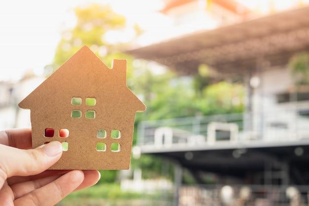 Modelo de casa en mano de agente de seguros de hogar