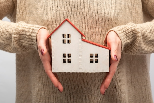 Modelo de casa en manos femeninas. vivienda propia, compra de concepto inmobiliario.