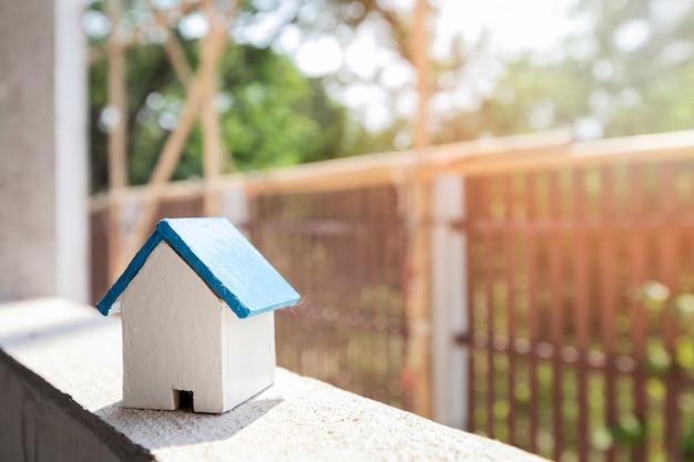 Modelo de la casa en el marco de la ventana en el sitio de construcción de viviendas.