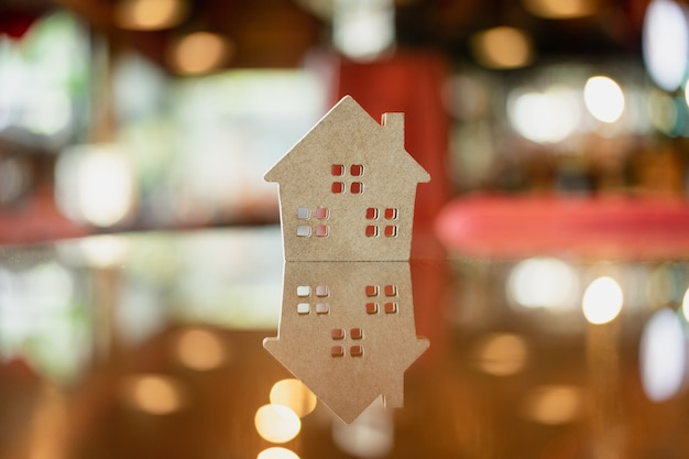 Modelo de casa en mesa de cristal con reflejo, símbolo de construcción.