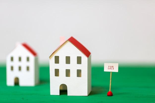 Modelo de casa en miniatura cerca de la etiqueta de venta en el escritorio con textura verde sobre fondo blanco