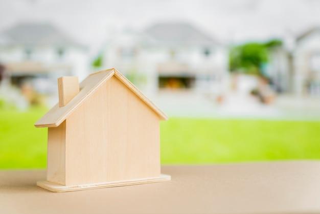 Modelo de casa en miniatura en mesa frente a casas suburbanas