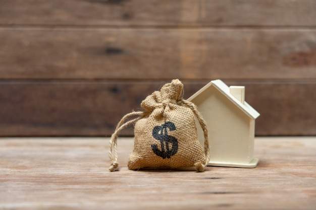 Un modelo de casa modelo se coloca en una pila de monedas. se utiliza como concepto de negocio de fondo.