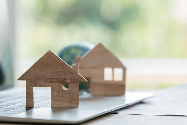 Modelo de casa modelos de casa de madera en computadora portátil con documentos de informe gráfico