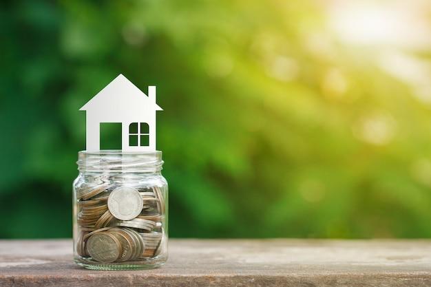 Modelo de casa en monedas en frasco de vidrio, ahorrando para comprar una casa