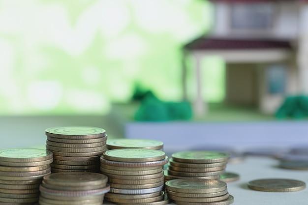 Modelo de casa con monedas en mesa de madera.