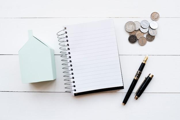 Modelo de casa de papel azul; diario en espiral; monedas y pluma estilográfica negra con tapa abierta sobre mesa blanca